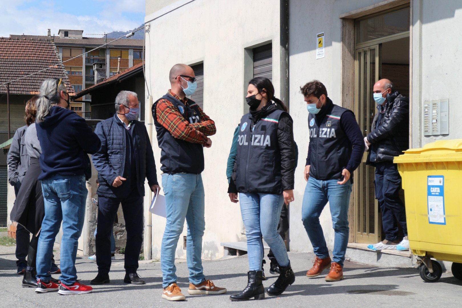 Gli inquirenti davanti il portoncino del condominio dove è avvenuto l'omicidio